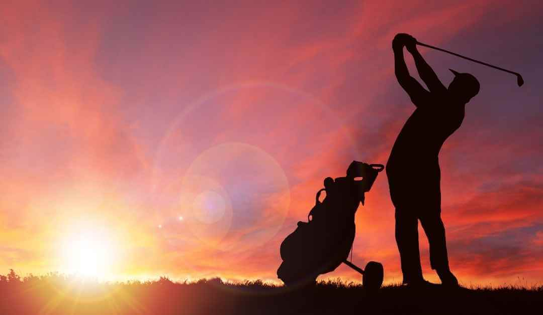 A man playing golf game in sunset/sunrise